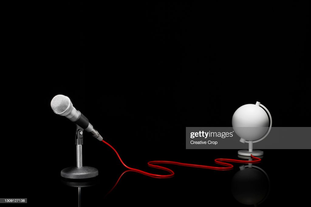 Microphone in a desktop stand connecting to a white globe on a tabletop : Stock Photo