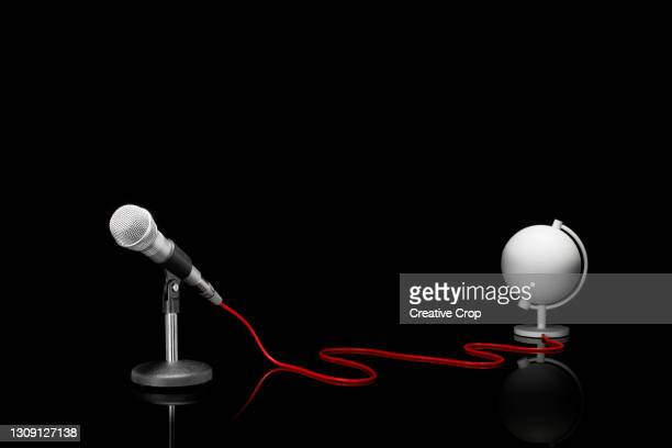 microphone in a desktop stand connecting to a white globe on a tabletop - microzoa stock pictures, royalty-free photos & images