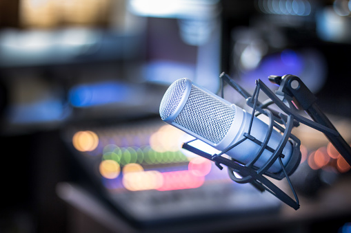 Microphone in a professional recording or radio studio, equipment in the blurry background 1130065303