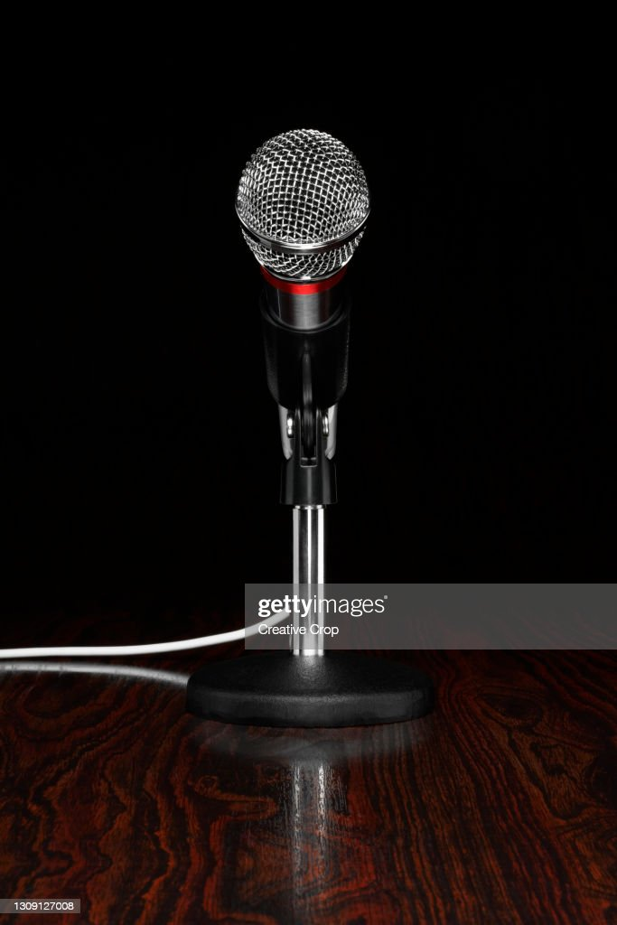 A microphone in a stand, on a wooden desktop : Stock Photo