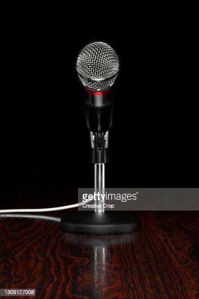 a microphone in a stand, on a wooden desktop - microzoa stock pictures, royalty-free photos & images