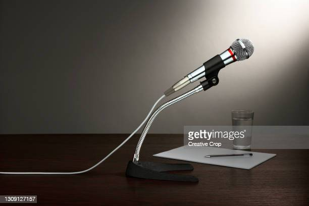 a microphone in a stand, with paper and a glass of water, all on a wooden desktop - microzoa stock pictures, royalty-free photos & images