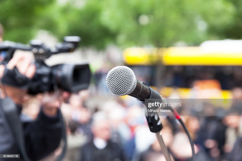 Microphone in focus against blurred crowd. Filming street protest. : Stock Photo