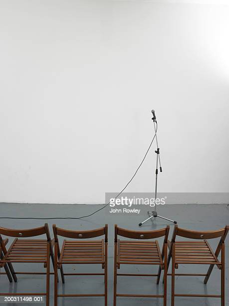 microphone in front of row of empty chairs - マイクスタンド ストックフォトと画像