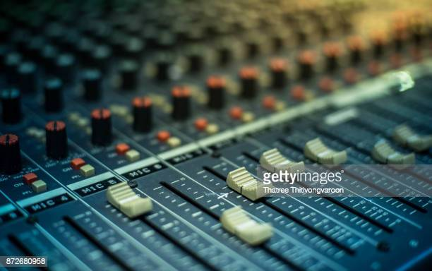 microphone over the abstract blurred on sound mixer out of focus background - sound recording equipment stock pictures, royalty-free photos & images