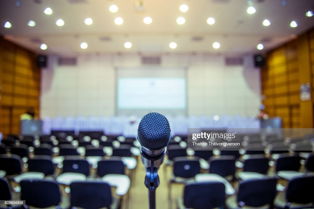 Microphone over the Abstract blurred photo of conference hall or seminar room background : Foto de stock