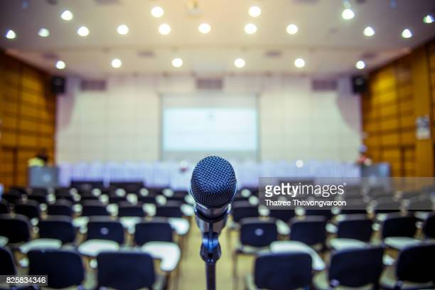 microphone over the abstract blurred photo of conference hall or seminar room background - press conference stock pictures, royalty-free photos & images