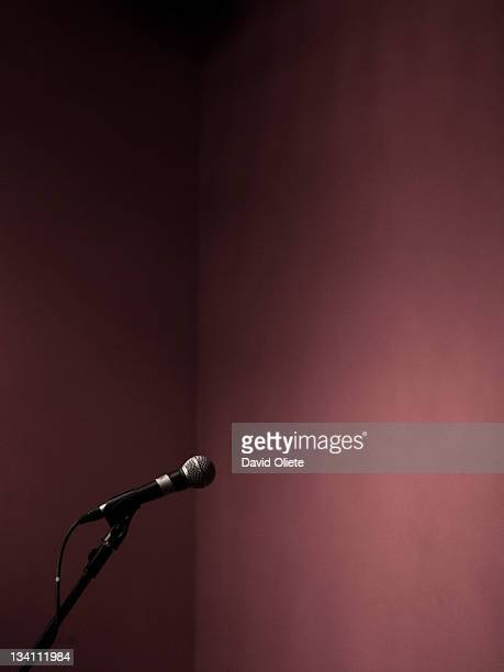 microphone standing in front of maroon wall - david oliete stock-fotos und bilder