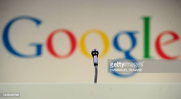 A microphone stands in front of a Google logo during a press annoucement at Google headquarters in New York May 21 2012 AFP PHOTO/Emmanuel Dunand