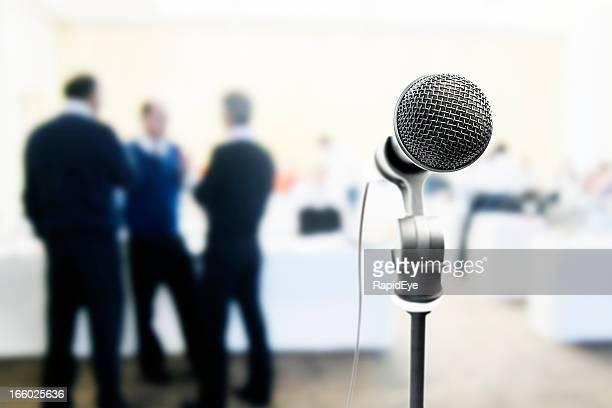 Microphone waits for speaker at meeting; male attendees stand behind