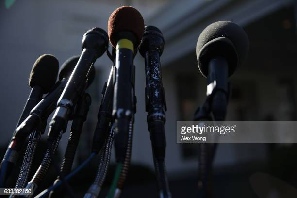 Microphones belong to different media outlets are set up on a stand in front of the West Wing of the White House January 31 2017 in Washington DC US...