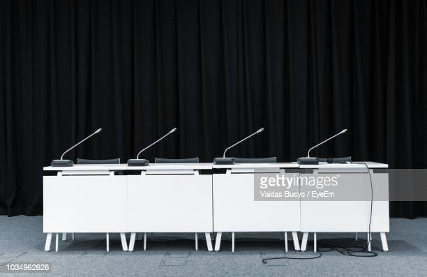 microphones on desk against black background - press conference stock pictures, royalty-free photos & images