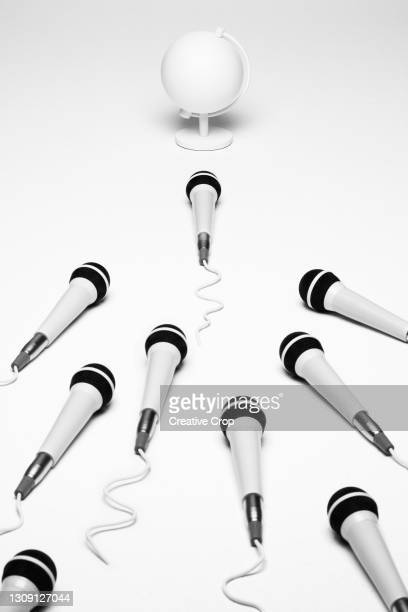 microphones point towards a desk globe - microzoa stock pictures, royalty-free photos & images
