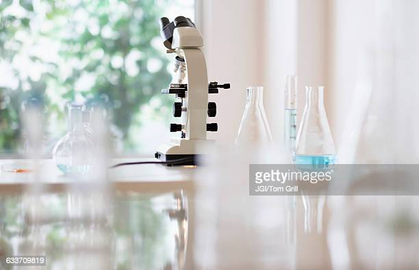 Microscope and beakers in laboratory