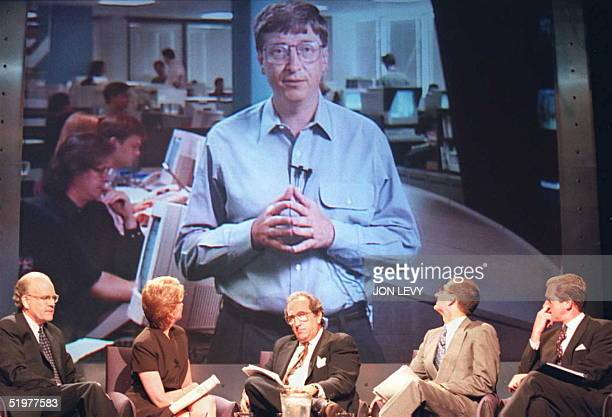 Microsoft CEO Bill Gates appears on a large screen TV during a press conference with NBC CEO Bob Wright NBC journalist Jane Pauley NBC News President...