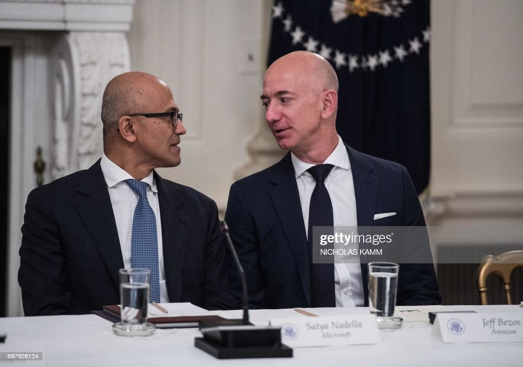 Microsoft CEO Satya Nadella (L) and Amazon CEO Jeff Bezos chat during an American Technology Council roundtable at the White House in Washington, DC, on June 19, 2017. /