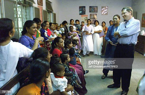 Microsoft chairman Bill Gates CoFounder of the Bill Melinda Gates Foundation talks to a group of mothers and their children September 14 2000 as...
