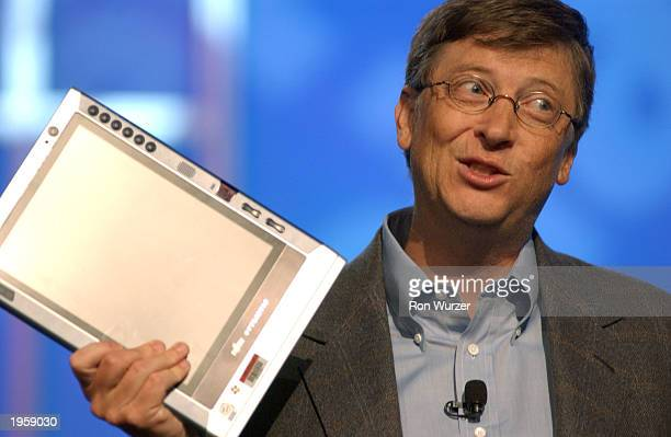 Microsoft Chairman Bill Gates holds a tablet PC as he speaks about newspapers and technology at the annual Newspaper Association of America's...