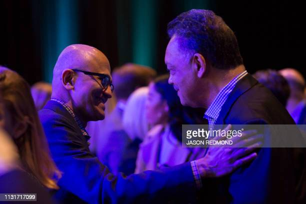 Microsoft Chief Executive Officer Satya Nadella and Rev Jesse Jackson talk before the start of Starbucks's Annual Meeting of Shareholders in Seattle...