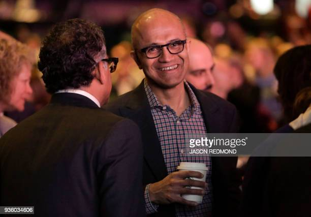 Microsoft Chief Executive Officer Satya Nadella talks to other guests before the Starbucks Annual Meeting of Shareholders at McCaw Hall in Seattle...