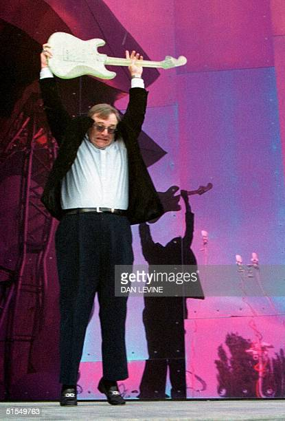 Microsoft cofounder Paul Allen christens his Experience Music Project museum by smashing a glass guitar during its grand opening 23 June 2000 in...