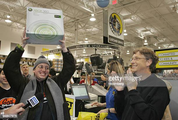 Microsoft Corp. Chairman Bill Gates, right, applauds as Dan Friedman holds up the first Microsoft Xbox 360 video-game console sold at a Best Buy...