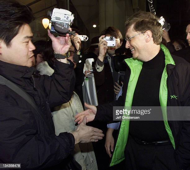 Microsoft Corp. Chairman Bill Gates shakes hands with people waiting in line to purchase the Xbox video game system February 22, 2002 in Tokyo.