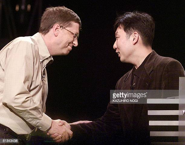 Microsoft Corp.'s co-founder Bill Gates shakes hands with Japan's Sega joint chief operating officer Tetsu Kayama during the keynote speech held by...