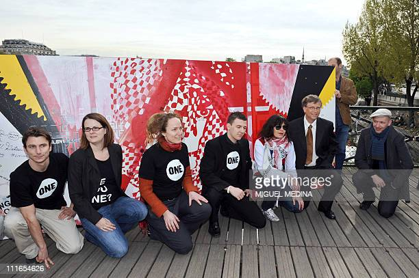Microsoft founder and philanthropist Bill Gates poses with artists including Dag and Russian Artof Popof in front of a painting on the Pont des Arts...