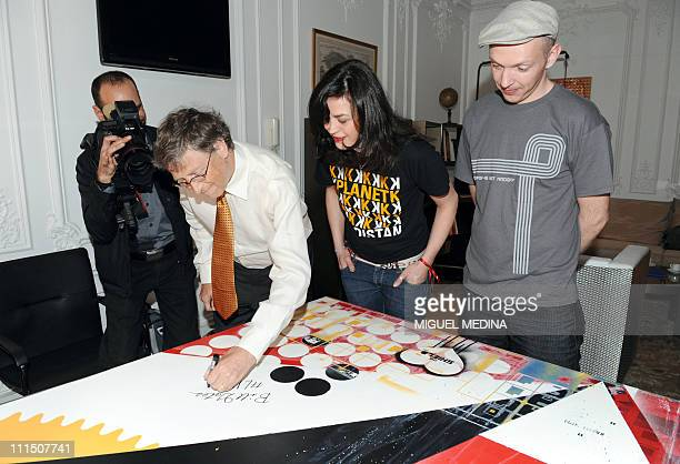 Microsoft founder and philanthropist Bill Gates signs a painting of two artists Dag and Russian Artof Popof on April 4 2011 in Paris as part of his...