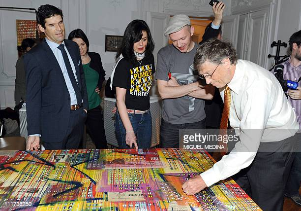 Microsoft founder and philanthropist Bill Gates signs a painting of two artists Dag and Russian Artof Popof next to Felix Marquardt president of...