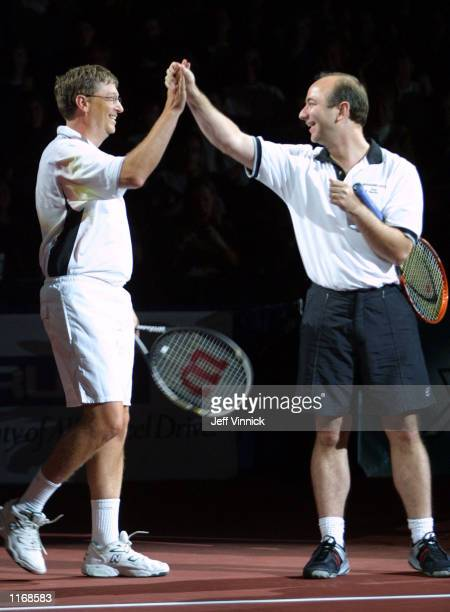 Microsoft founder Bill Gates and Amazon.com founder Jeff Bezos high-five prior to their celebrity pro-am set during the Schick XTreme III Tennis...