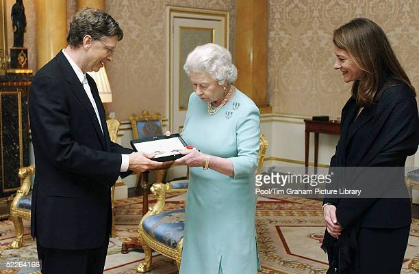 Microsoft founder Bill Gates and his wife Melinda pose for photographs after Gates is awarded an honorary knighthood at Buckingham Palace on March 2...