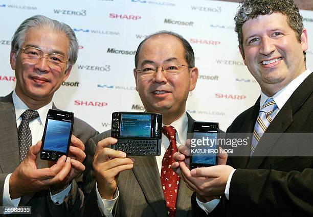 Microsoft Japan President Darren Huston, Willcom President Yoichiro Yatsurugi, and Sharp Corp. Executive Manager Masashi Matsumoto, show the portable...