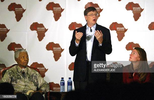 US Microsoft owner Bill Gates addresses a youth forum on HIV/AIDS at the University of Witwatersrand in Johannesburg 22 September 2003 as his wife...