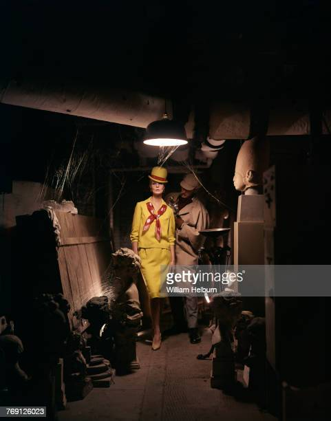 Fashion model Angela Howard Helburn poses in a mustard yellow skirt blouse and darby hat standing next to a model dressed as detective Sherlock...