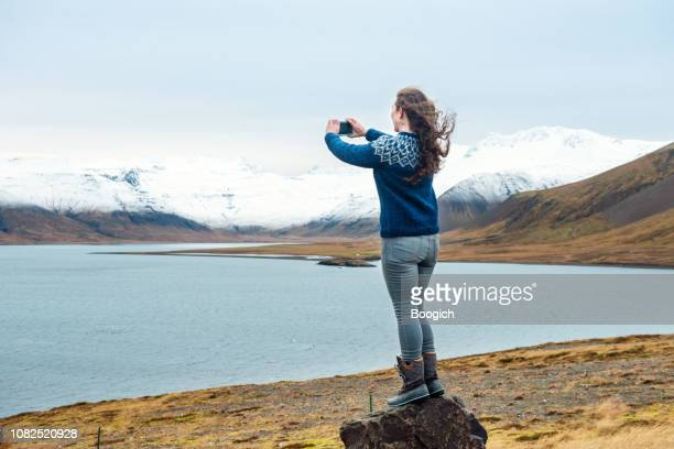 mid 30s american woman traveling iceland enjoys view of landscape - eco tourism stock pictures, royalty-free photos & images