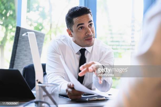 hombre de negocios de mediados de los años 30 explicando los méritos del plan a su colega - persuasión fotografías e imágenes de stock