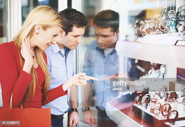 Mid 30's couple looking at jewelery store.