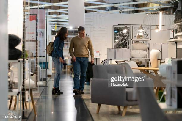 mid adoult couple walking at a furniture store while talking and smiling - furniture stock pictures, royalty-free photos & images
