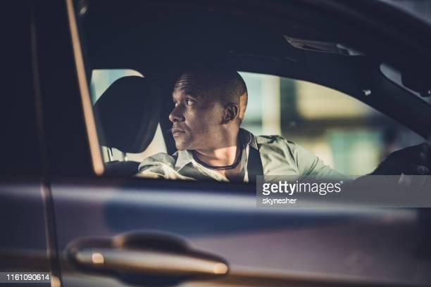 mid adult afro-amerikaanse zakenman parkeren zijn auto in omgekeerde richting. - mid volwassen stockfoto's en -beelden