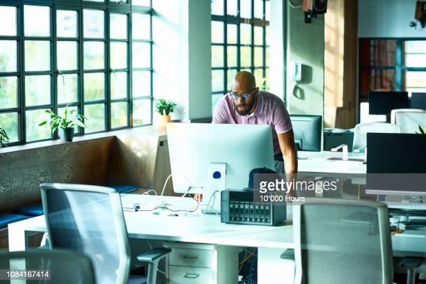 mid adult african man using computer at desk in office - inclinar se pose imagens e fotografias de stock