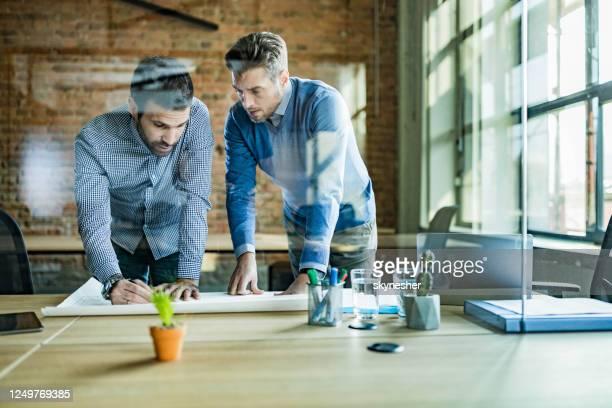 mid volwassen architecten analyseren van blauwdrukken in het kantoor. - netjes informeel stockfoto's en -beelden