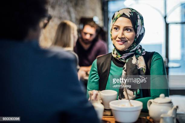 Mid adult Asian woman in cafe with friend smiling