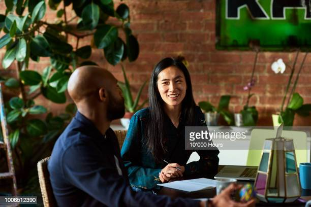 mid adult asian woman smiling towards male colleague - interview stock pictures, royalty-free photos & images