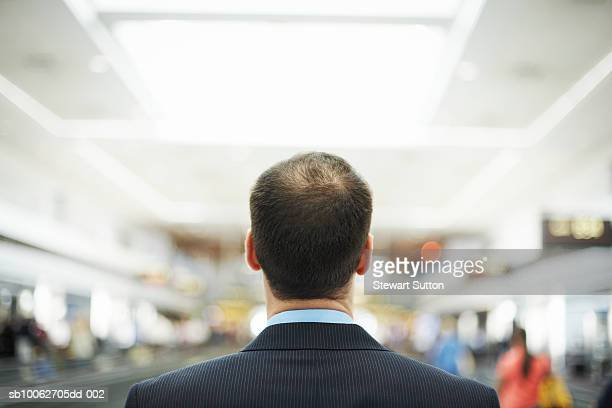 Mid adult balding business man standing at airport, rear view