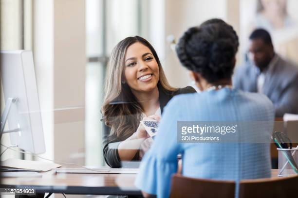a mid adult bank manager helps mature woman open account - bank customer stock pictures, royalty-free photos & images