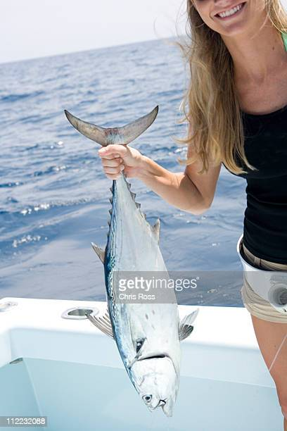 A mid adult blonde woman smiles as she holds up her freshly caught jack tuna.