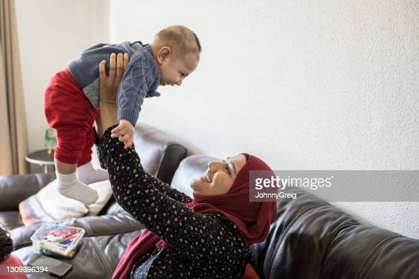 mid adult british asian mother lifting her laughing baby boy - religious dress stock pictures, royalty-free photos & images