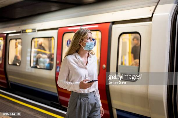 mid adult british businesswoman waiting on subway platform - long hair stock pictures, royalty-free photos & images